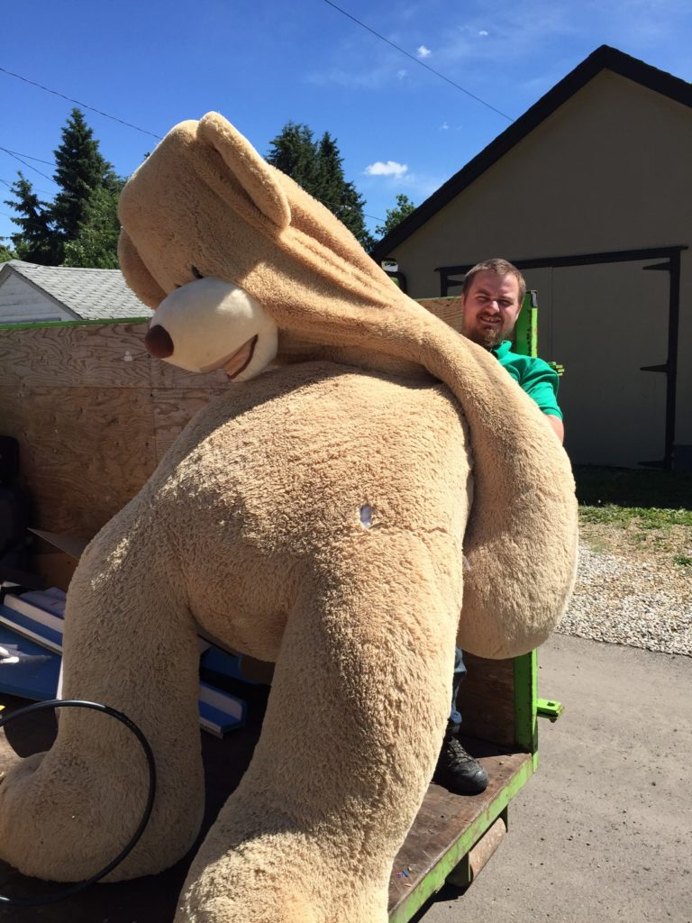 Our staff member holds a teddy bear that is twice his size found at a junk removal in Edmonton.